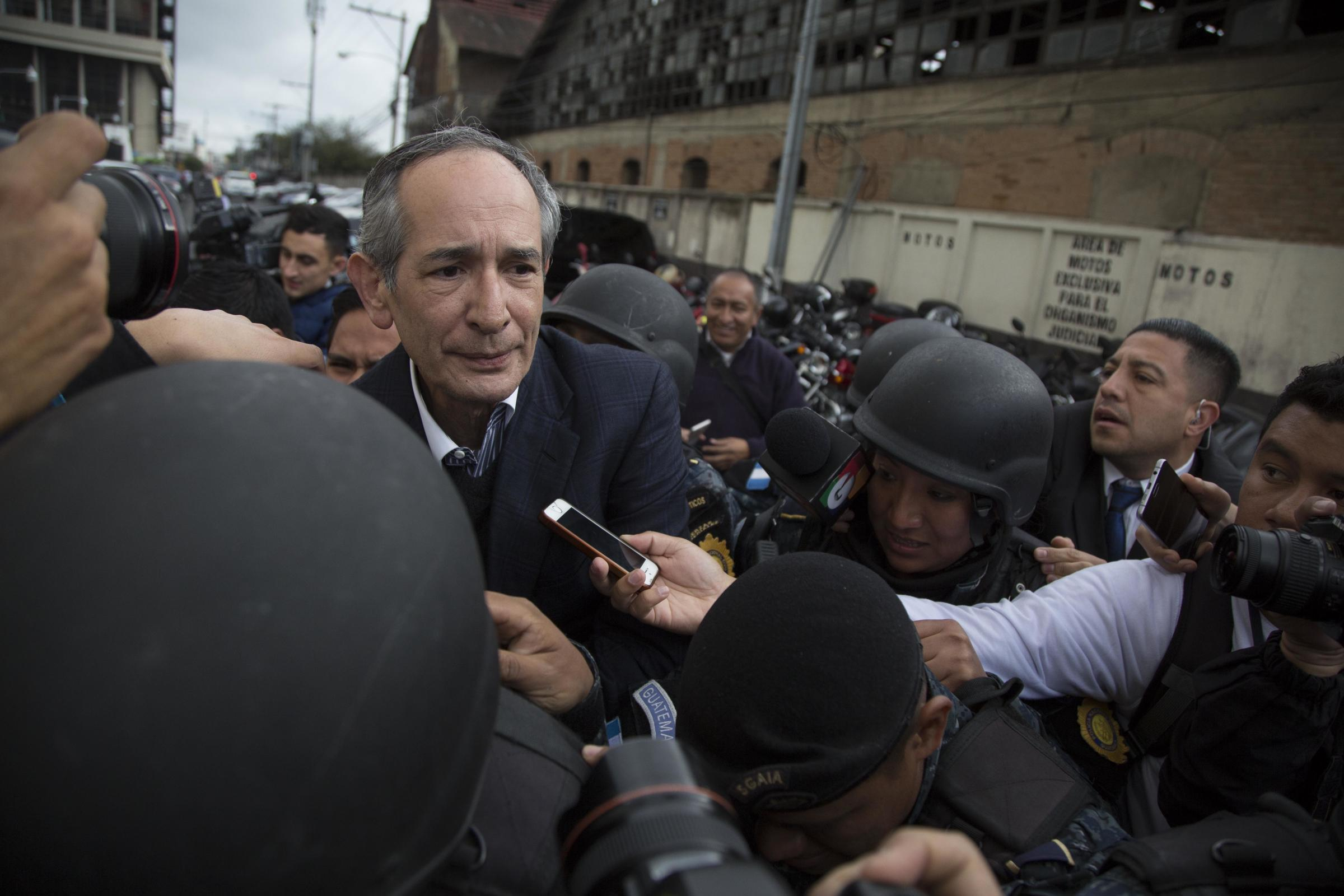 Alvaro Colom is escorted by police to a courtroom in Guatemala City (AP/Luis Soto)